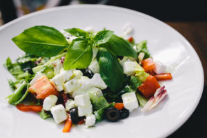 Salade de feta poivron, olive et basilique sur une assiette.